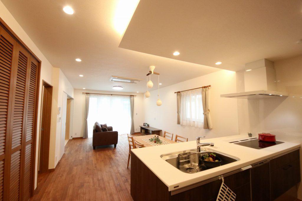 オリジナルの無垢の床と漆喰のLDK。 折り下げ天井に間接照明を合わせたキッチンスペース。