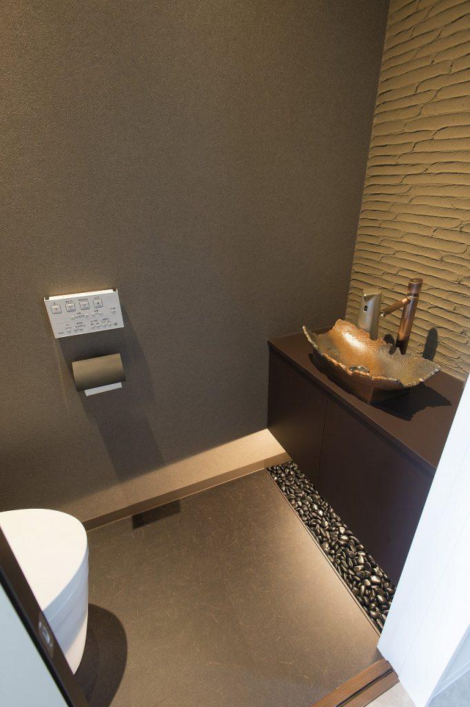 キャビネットの下には玉砂利を敷き、間接照明を合わせて。 造作の手洗いや壁の使用した薩摩中霧島の風合いとも良く合います。