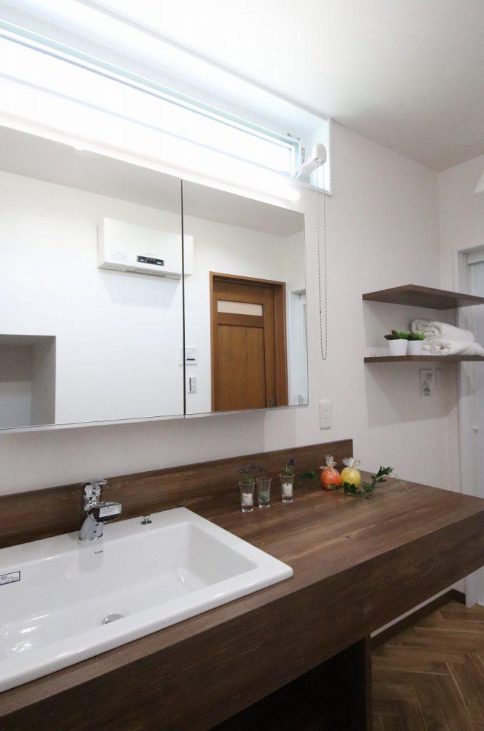 木の天板と陶器のボウルの造作洗面台に、 レトロモダンな雰囲気になるヘリンボーンの床を合わせました。
