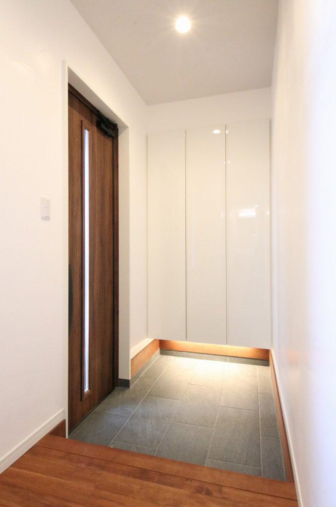 ホワイトの収納スペース下に間接照明を配置。雰囲気のある玄関周りに