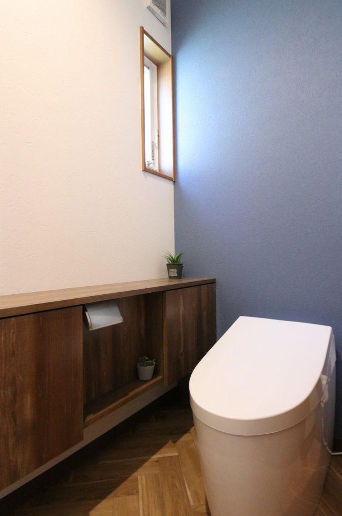 トイレにもヘリンボーンの床を採用。 深い藍色のアクセントクロスでクラシカルで上品な雰囲気に。