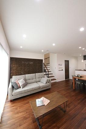 真っ白な漆喰の壁とダークブラウンのオリジナルの無垢の床で、落ち着いた雰囲気のリビング。
