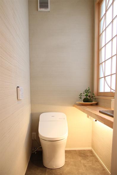 壁は薩摩中霧島を使用した和テイストのトイレ。坪庭に面した窓から木陰が映る