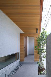 玄関までのアプローチの軒天井を板張りに。この板張りの天井が室内へ続きます。