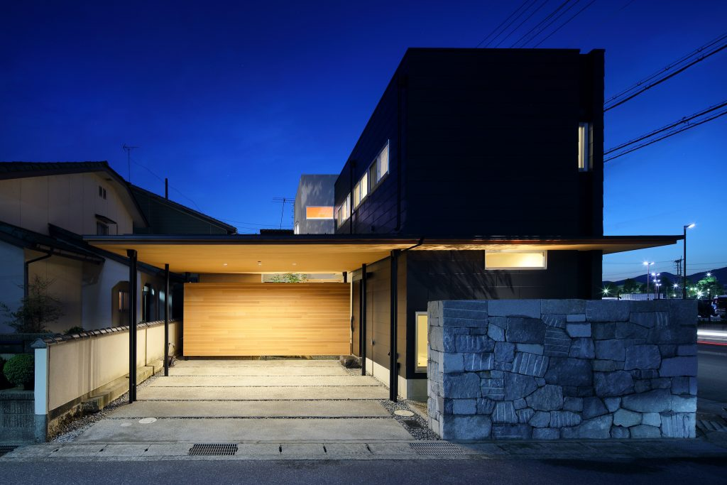 夜になると、外壁の黒とガレージの木の素材のコントラストが美しい外観