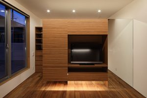 寝室の造作テレビボードはウォークインクローゼットとの仕切りも兼ねた設計に
