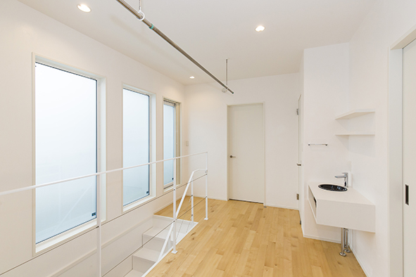 オープン階段をあがると開放的なホールになった階段ホールは、室内干しもでき、サンルームのような空間に。またすりガラスの外はベランダになっています。