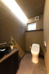 間接照明のほんのりした光のグラデーションが楽しめるトイレ。室内は、デザイン性だけでなく、調湿・消臭効果もある薩摩中霧島で仕上げています。
