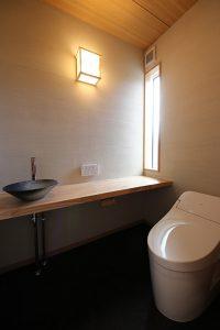手洗いを造作で仕上げた和のテイストのトイレ。壁は薩摩中霧島。
