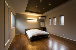 ブランベースのシックな落ち着いた寝室。折り上げ天井と間接照明も設けゆったりくつろげる空間に。