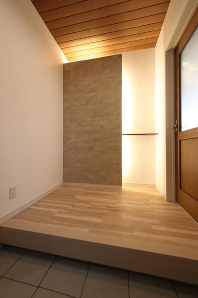 石張りの壁の裏に間接照明をあてることで高級感を演出した玄関ホール