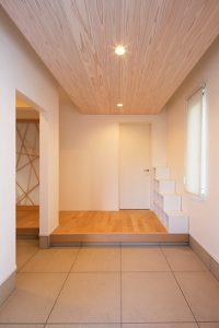 天井を板張りにしたことで、暖かくナチュラルな雰囲気の玄関ホール。造作の下駄箱がアクセントに。