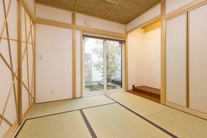 中庭を挟んで配置されたモダンな印象の和室。天井は網代、壁は漆喰仕上げ。