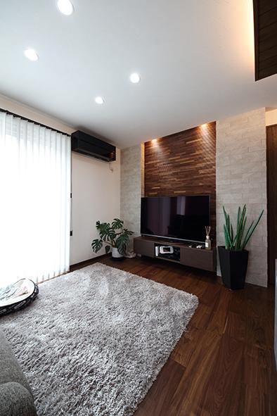 造作のテレビボードの壁面にウッドタイル、エコカラットを張ったリビングスペース。間接照明が入れられているので、タイルの壁の凹凸が強調され陰影がとても素敵です。