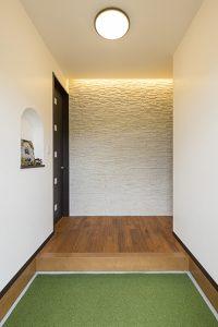 正面の石張り壁に間接照明を入れた玄関ホール。凹凸に光が当たり幻想的に。