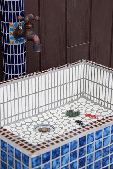 モザイクタイルで仕上げた立水栓。2匹の金魚が泳ぐ遊び心のあるガーデンシンク。