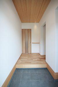 天井を板張りにした暖かみを感じられる玄関ホール。正面にはウェルカムカウンターを造作。