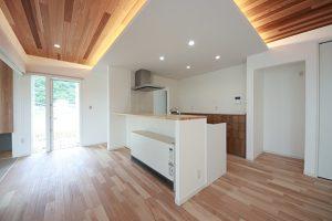 回遊できるキッチンの天井部分は、木を楽しむ板張り仕上げに折り下げ天井に間接照明をプラス。