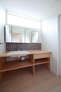 造作洗面台。白の陶器に、木製の洗面台とタイルを使用しナチュラルな仕上げに。
