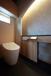 和室の床の間などにも取り入れられることの多い、アーチの下がり壁に間接照明を入れた和モダンのトイレ。