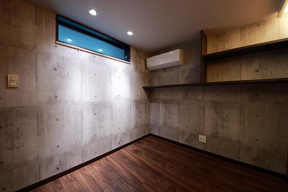 無骨な印象があるコンクリート調の壁で仕上げた隠れ家的な書斎スペース。ピクチャーレールを付け、お気に入りの洋服をディスプレイできるようになっています。